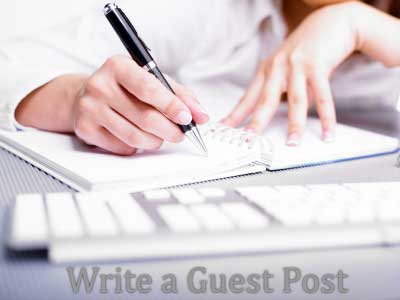 A hand with a pen writing a guest post on a notepad
