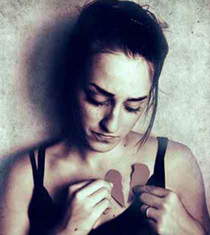 a girl holding broken apart pieces of heart in her hand