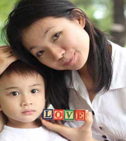 mother caressing her child and holding blocks showing letters love teacher