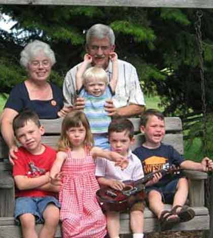 grandparents standing behind a swing being full of their grandchildren seated on it