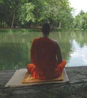 a Buddhist monk meditating near a river bank to find peace within himself