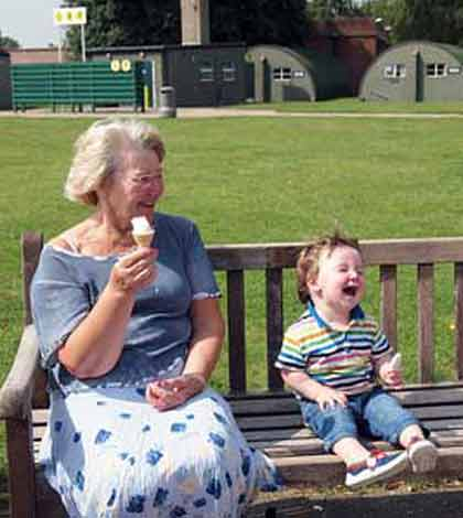 Grandmother sitting along with grandchild on a bench eating ice-cream and having fun
