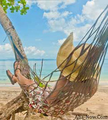 A woman on a hammock by the beach sending a message you can make your life easier if you take it easy