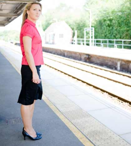 Upset mother keeping calm and standing at platform waiting for the train