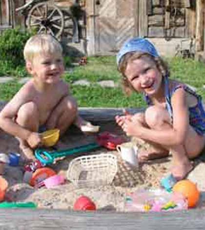 two children behave like real children playing and having fun in the sandpit
