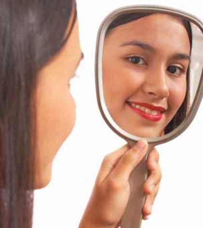 Girl holding mirror and asking am I beautiful with a smile