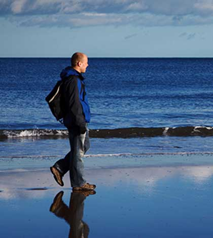 Man walking on the beach trying to make a difference.