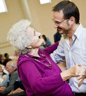 a young man take care of elderly lady and dancing with her