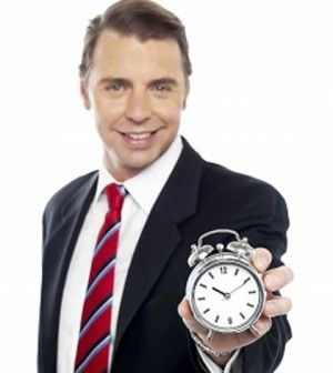 the father standing with a time clock in hand