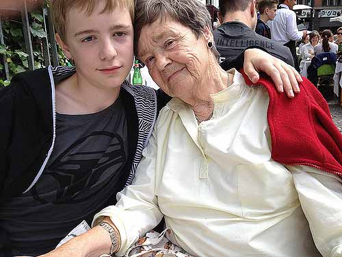 a young boy taking care of and loving his grandmother