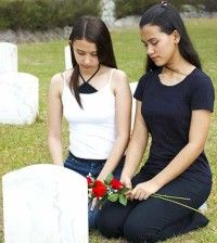 two girls sitting near a grave mourning the loss of a loved one