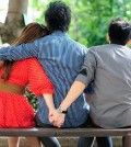 a man sitting with arms over a woman who secretly is having an affair holding hands with her lover