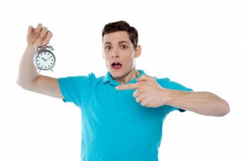 Man showing finger towards clock for time management