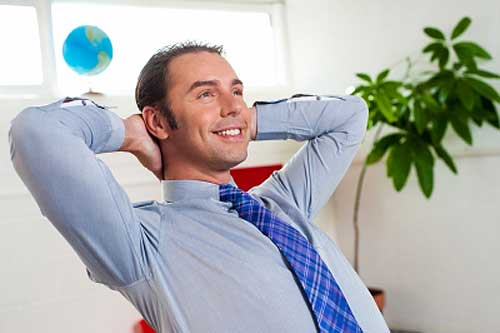 Man with hands at back of forehead relaxing in office