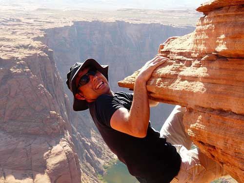 man climbing cliff height with bare hands
