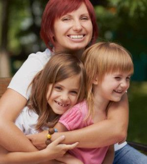 mother holding two joyful kids in arms