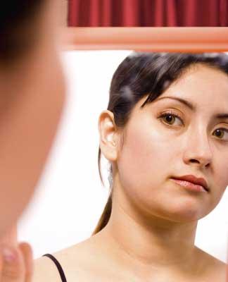 Woman looking into mirror not feeling good