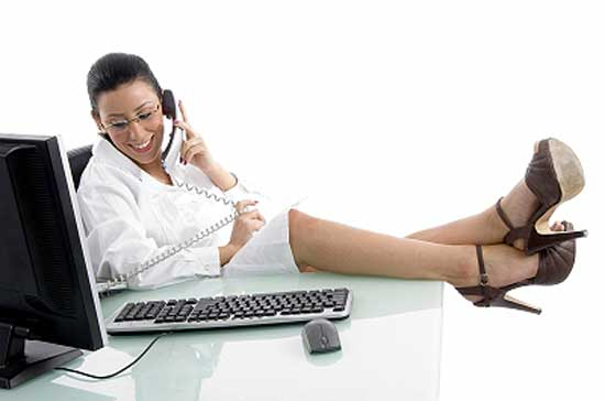 woman sitting at office desk with feet on table and chatting on phone