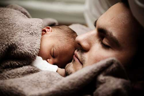man playing role of the father by taking care of baby