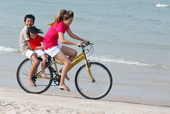 Mother riding bicycle with kids at the back on a beach during vacations