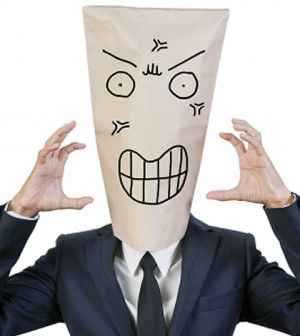 Man wearing a paper mask of anger