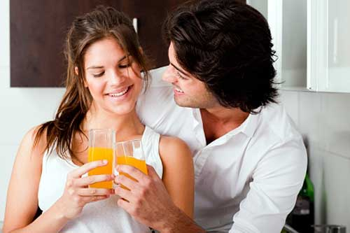 husband and wife clink juice glasses and share happy moments
