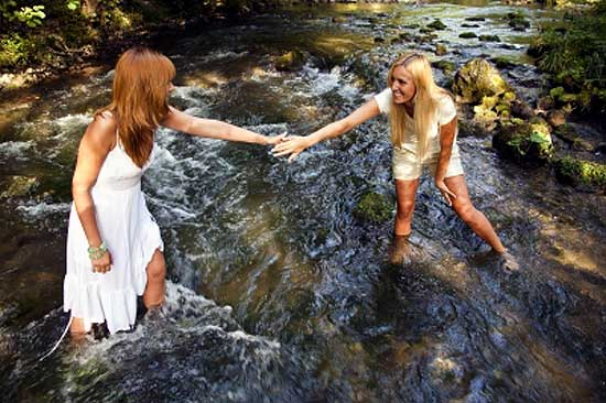 one girl helping other girl to cross stream