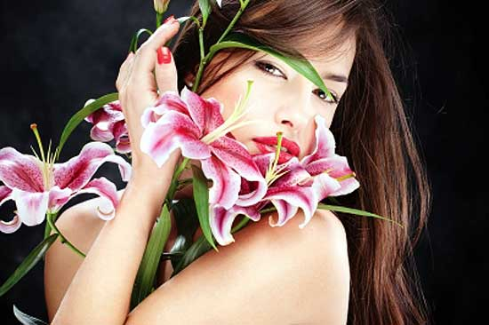 woman smelling flowers to relieve stress