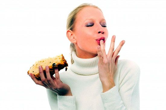 A woman licking fingers as tasty food makes her feel good.