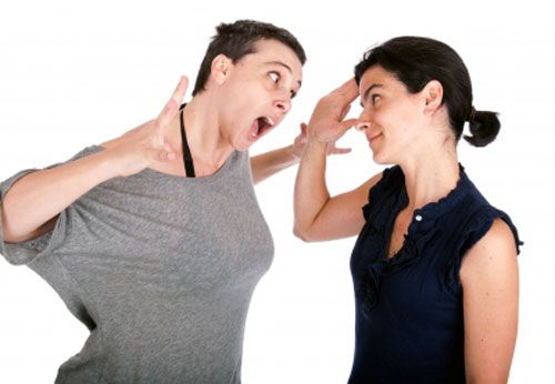 Woman smiling and trying to deal with anger as other gets angry
