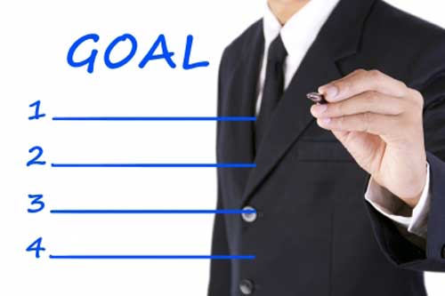 man setting goals by writing them