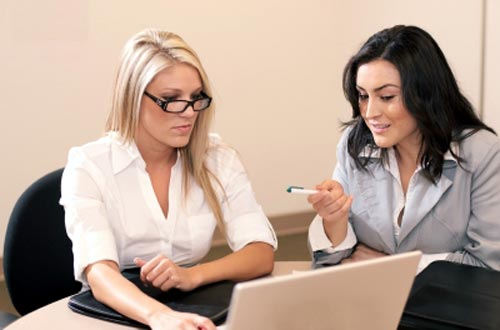 two women sharing problems online on laptop