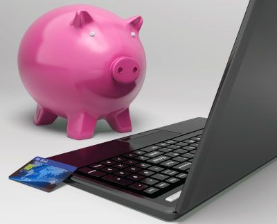 Piggy bank and laptop shown with credit card depicting blogging problems