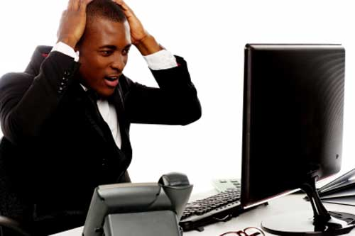 A black blogger holding his head viewing blog on desktop