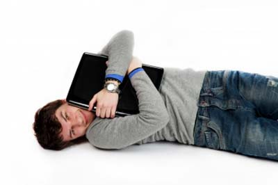 A man lying with laptop in arms