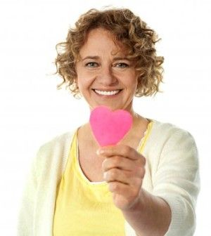 A woman organ donor with a paper heart in hand