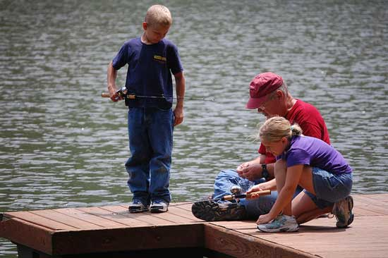 Grandparent and grandchildren fishing together.