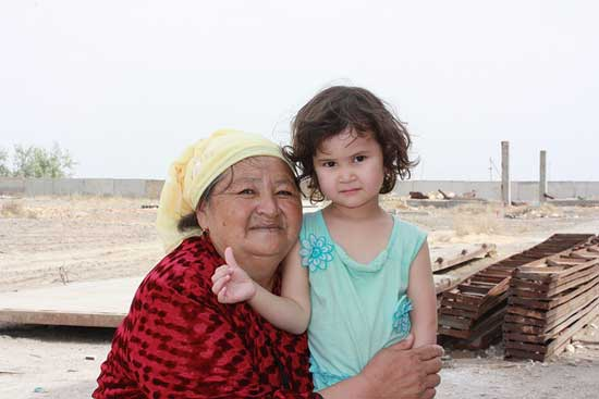 Grandchild standing with grandmother