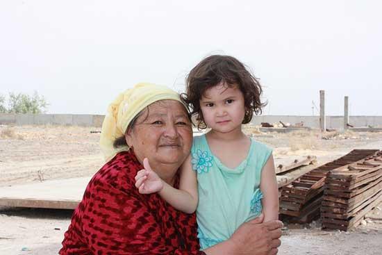 Grandchild standing with grandmother