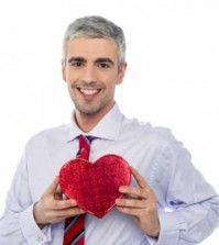 A man holding a heart toy in hand