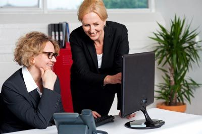A woman helping other woman on computer in office