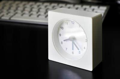 A clock placed in front of a blogger's computer.