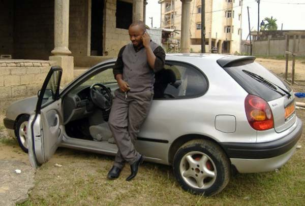 Enstine Muki standing with his car
