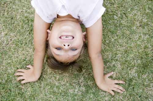 A child upside down and smiliing
