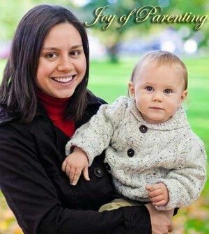 Mother holding baby in arms using effective parenting tips.