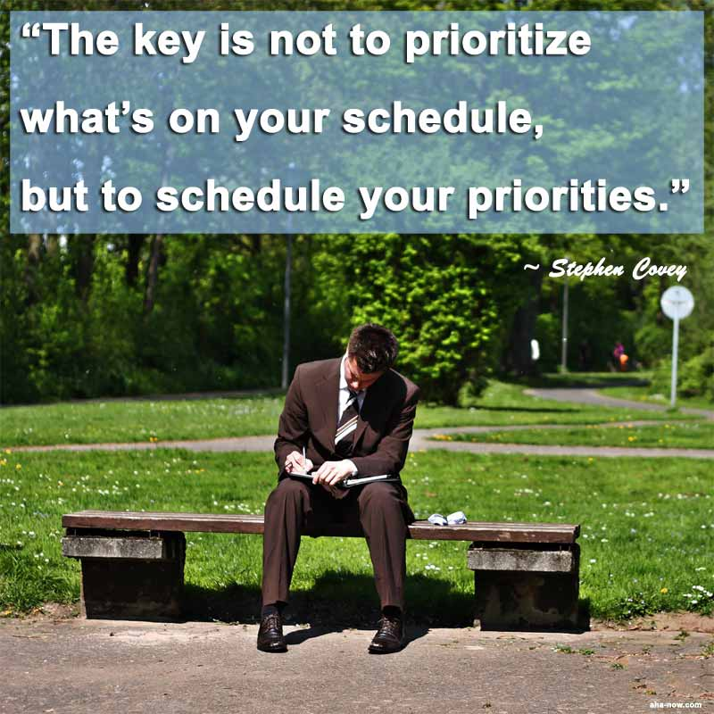 Man sitting on bench in park scheduling priorities in a diary