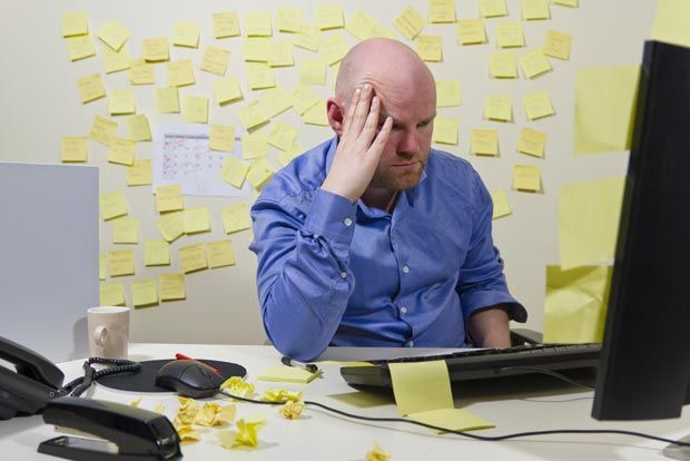 Man upset by too many post-it notes in home office