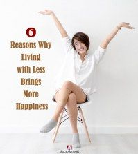 A women happy with her minimalist living sitting on a chair living with less.